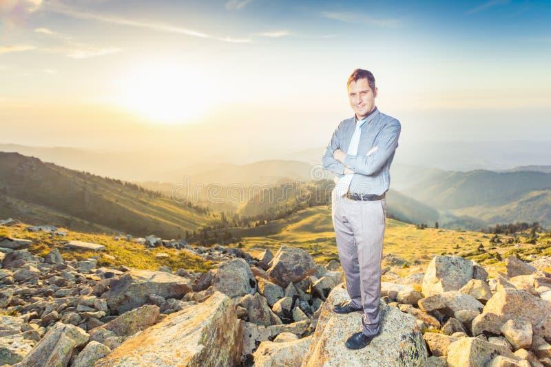 在看照相机的山顶部的成功的商人 免版税库存照片