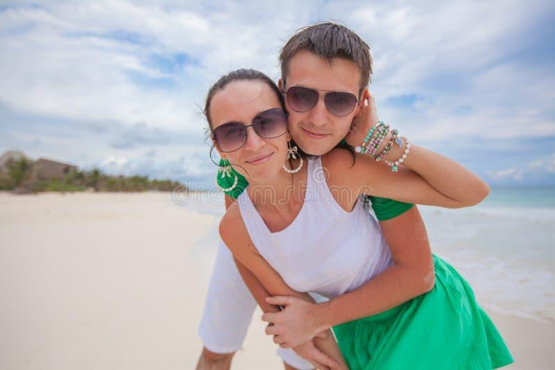 在看照相机的异乎寻常的海滩的愉快的夫妇 免版税库存图片