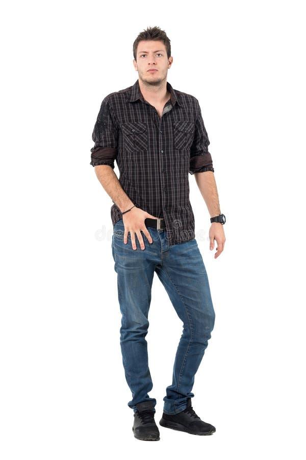 在看照相机的牛仔裤和格子花呢上衣的凉快的强壮男子的偶然男性模型 免版税库存照片