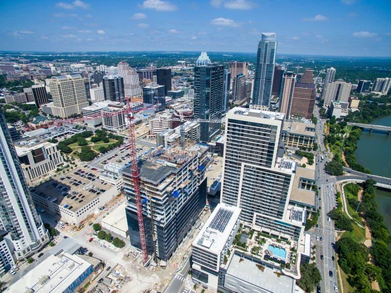 在看的上流下来在修建新的摩天大楼的建筑用起重机空中寄生虫视图上在奥斯汀得克萨斯 免版税库存图片