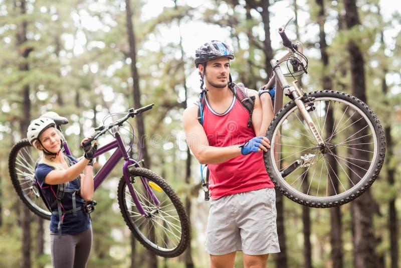 在看的自行车的年轻愉快的夫妇搬走骑自行车 库存图片