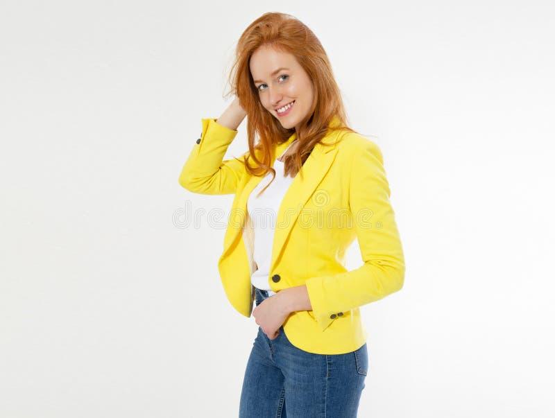 在看确信与微笑的照相机和接触她的头发的被隔绝的背景的年轻愉快的美丽的红色头发妇女 免版税库存图片