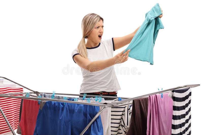 在看衬衣的衣物机架烘干机后的震惊妇女 图库摄影