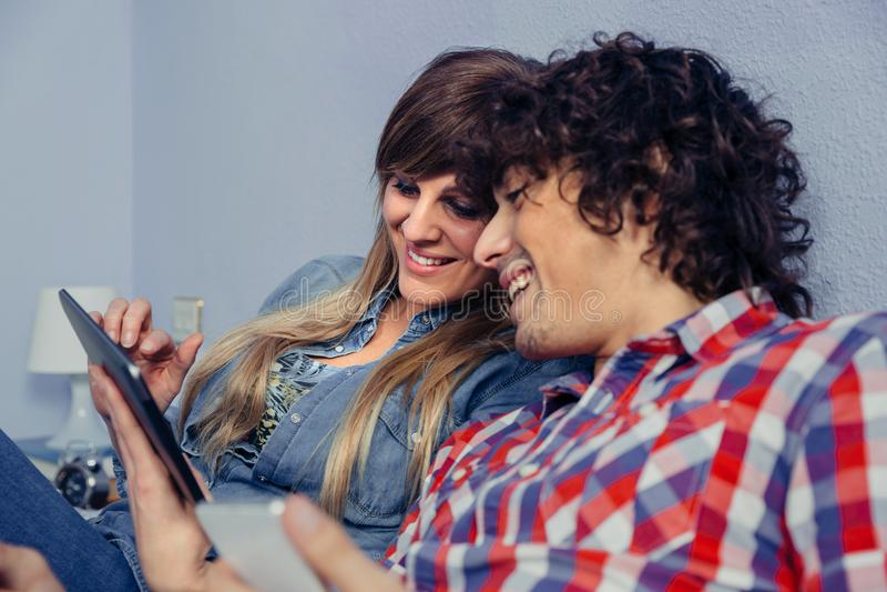 在看起来电子片剂和笑的爱的夫妇 库存照片
