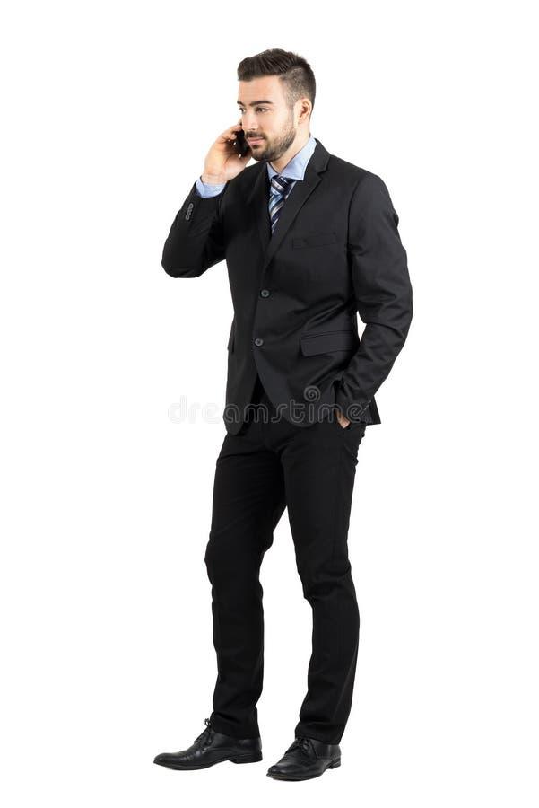 在看起来去侧视图的电话的英俊的有胡子的严肃的商人 免版税库存照片