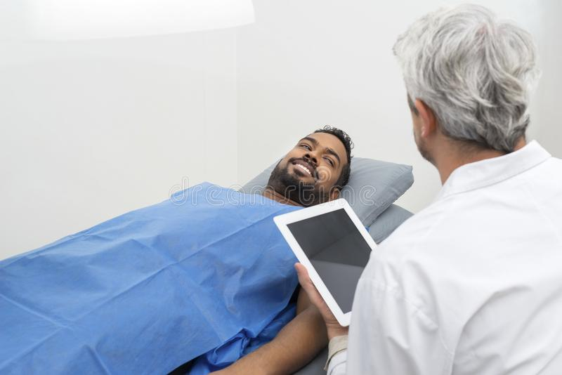 在看Using Digital Tablet医生的床上的患者 库存照片