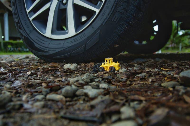 在真正的汽车旁边的黄色拖拉机玩具 免版税库存照片