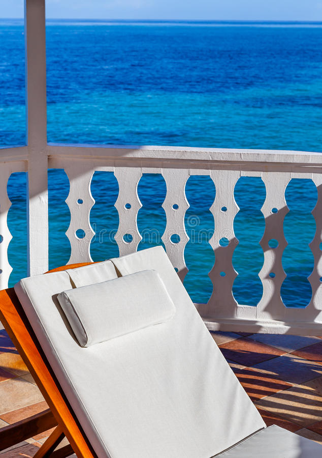 在眺望台的白色海滩睡椅有蓝色海洋背景 库存照片