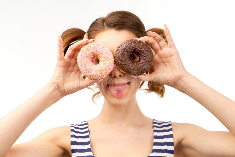 在眼睛前的有吸引力的少女藏品给油炸圈饼上釉,并且乐趣微笑显示舌头 在被隔绝的背景的特写镜头画象 库存图片