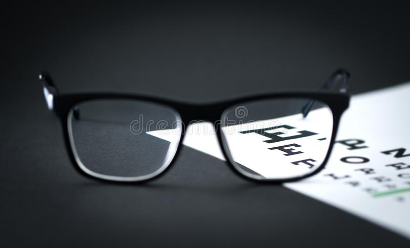在眼睛测试信件图的玻璃在眼镜师桌上 库存图片