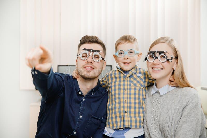 在眼科医生任命的愉快的年轻家庭 牛仔布衬衣的爸爸有黑发的显示注视食指的方向 免版税库存照片