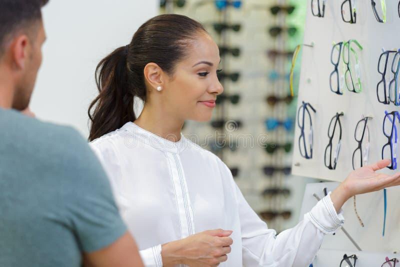 在眼镜师的男人和妇女估价的镜片 免版税库存图片
