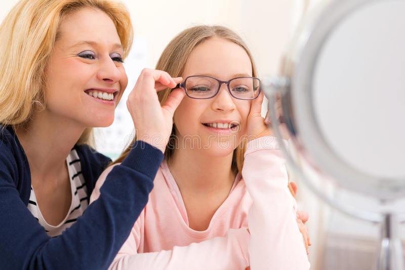 在眼镜师w的年轻小女孩尝试的玻璃她的母亲 免版税库存照片