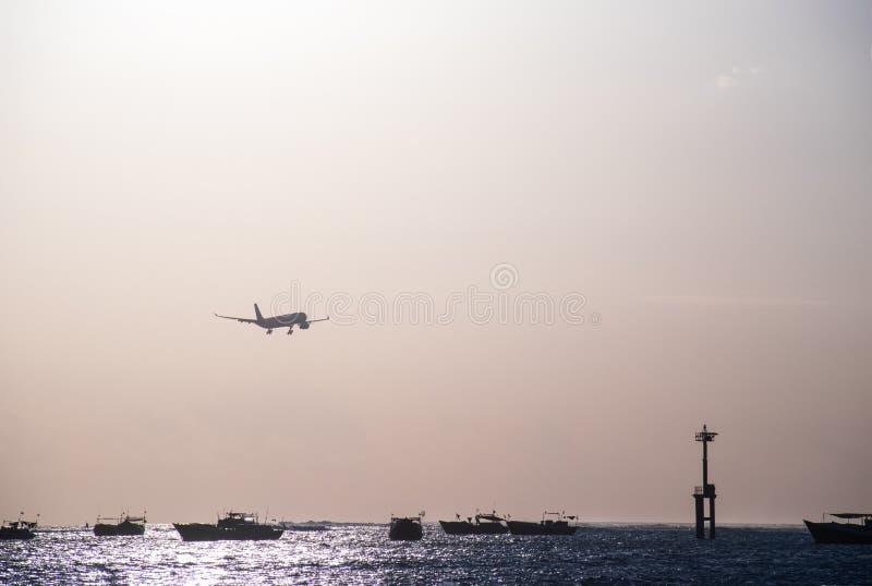 在着陆期间的飞机在日落 免版税库存照片