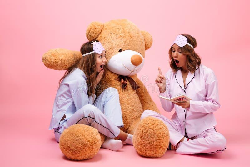在睡衣打扮的两个微笑的女孩 免版税库存图片