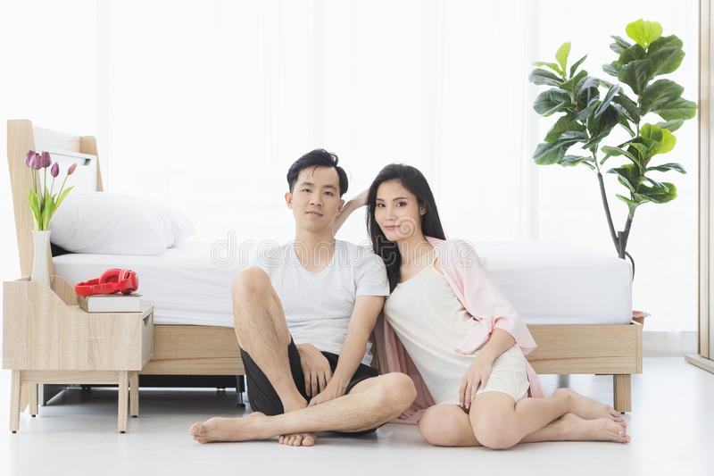 在睡衣的性感的夫妇坐地板在卧室 免版税库存照片