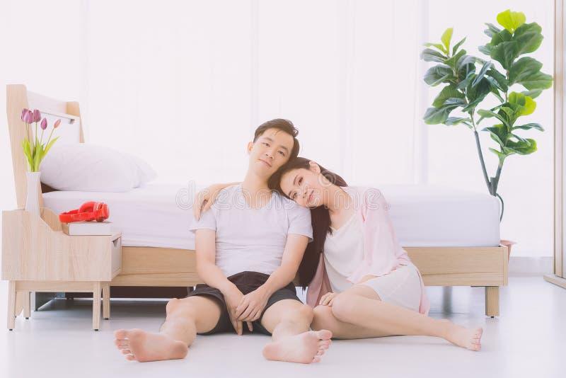 在睡衣的性感的夫妇坐地板在卧室 库存图片