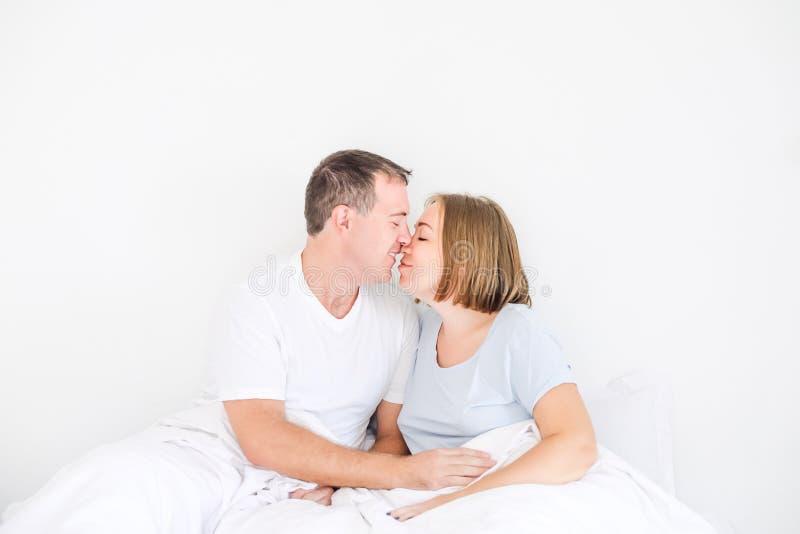 在睡衣裤的逗人喜爱的夫妇在床上 握在他怀孕的妻子的胃的丈夫手 愉快和爱恋的家庭早晨概念 库存图片