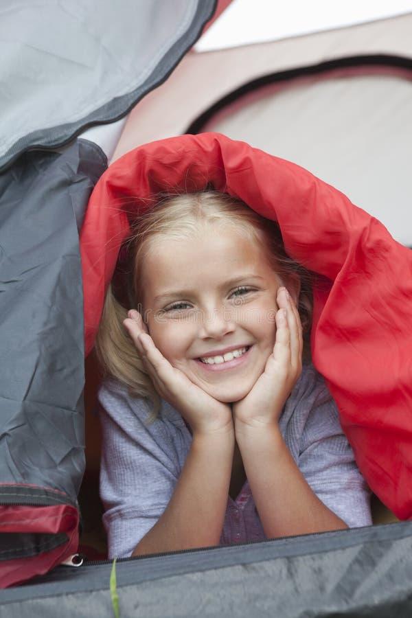 在睡袋下的女孩从帐篷微笑 免版税图库摄影