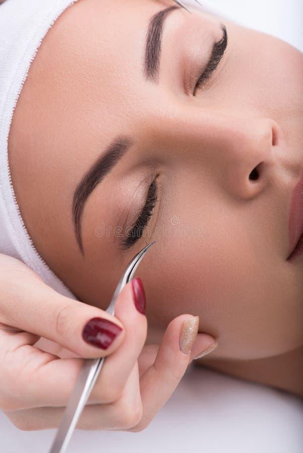 在睫毛引伸期间的美丽的少妇 免版税库存图片