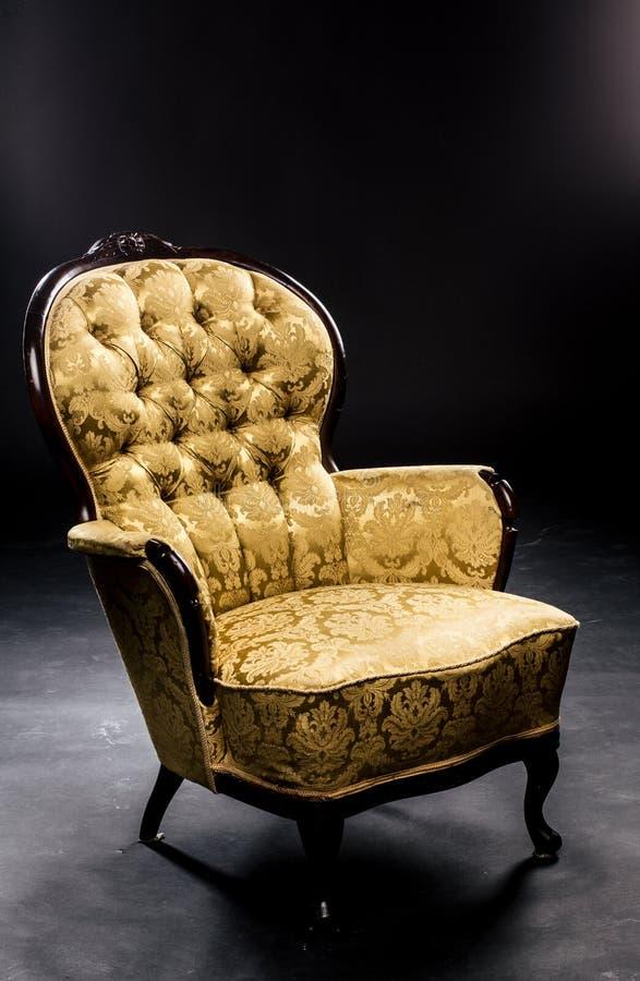 在短的腿芥末颜色美好的材料,纹理,木头的葡萄酒椅子 工作室,黑色背景 免版税库存图片