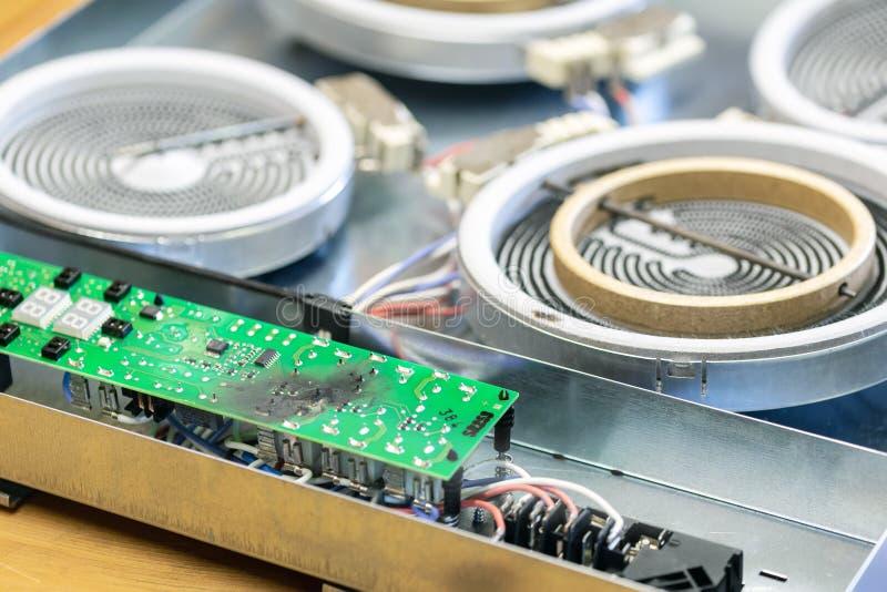 在短路以后的被烧的绿色微集成电路由于水损伤 厨灶损坏的过热控制板板  免版税库存照片