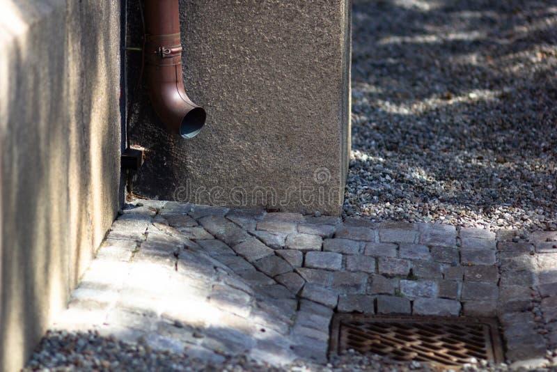 在石墙上的落水管雨水的 免版税图库摄影
