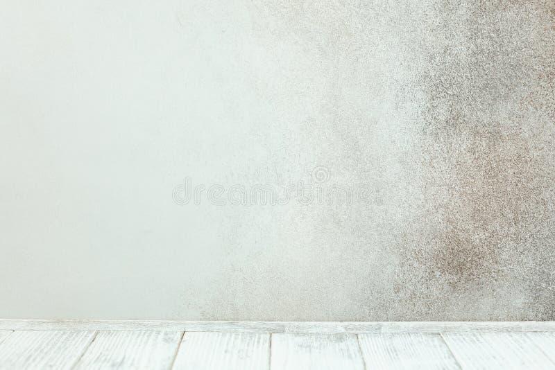 在石墙前面的空的白色木桌 库存照片