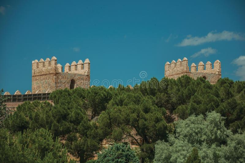 在石墙和树梢的城垛在阿维拉 免版税库存照片