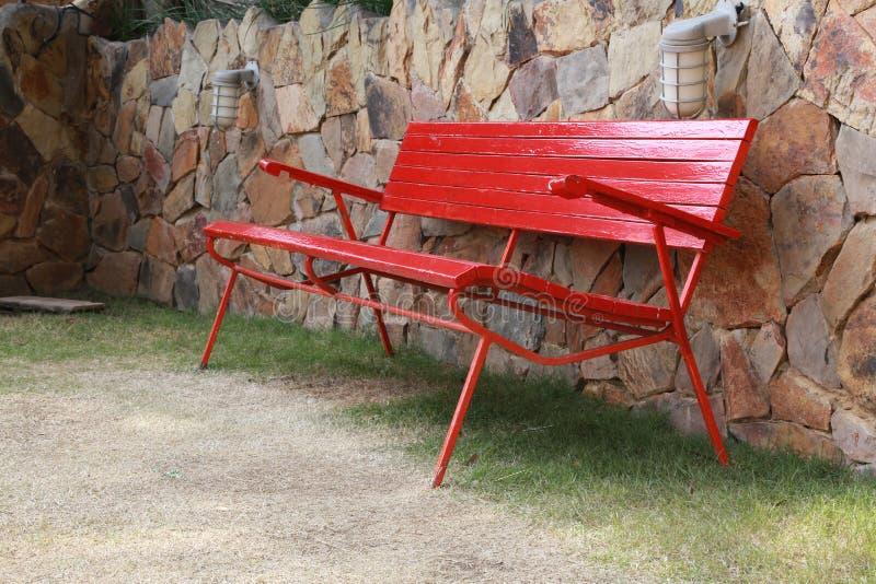在石墙旁边的红色长凳 库存图片
