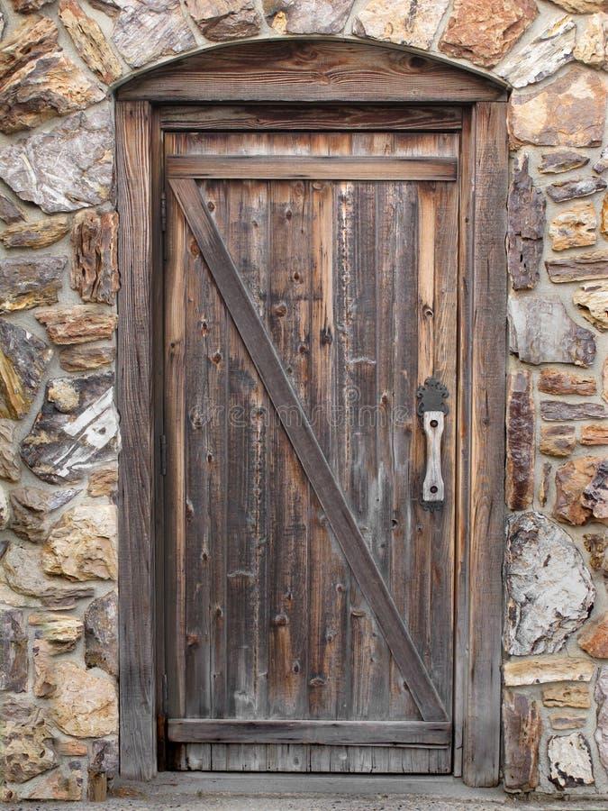 在石墙的老木门 免版税库存照片
