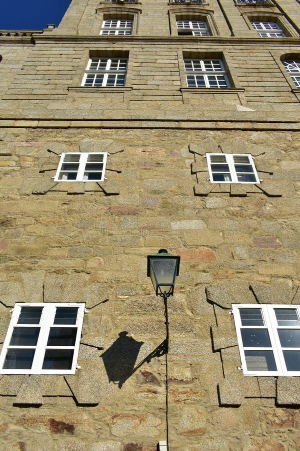 在石墙的老路灯到底有接近大教堂的白色窗口的 城镇厅,圣地亚哥-德孔波斯特拉,西班牙 晴朗的日 库存图片