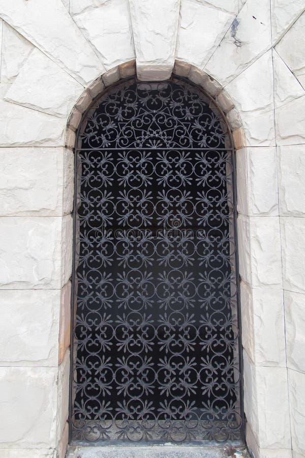 在石墙的钢门 免版税库存图片