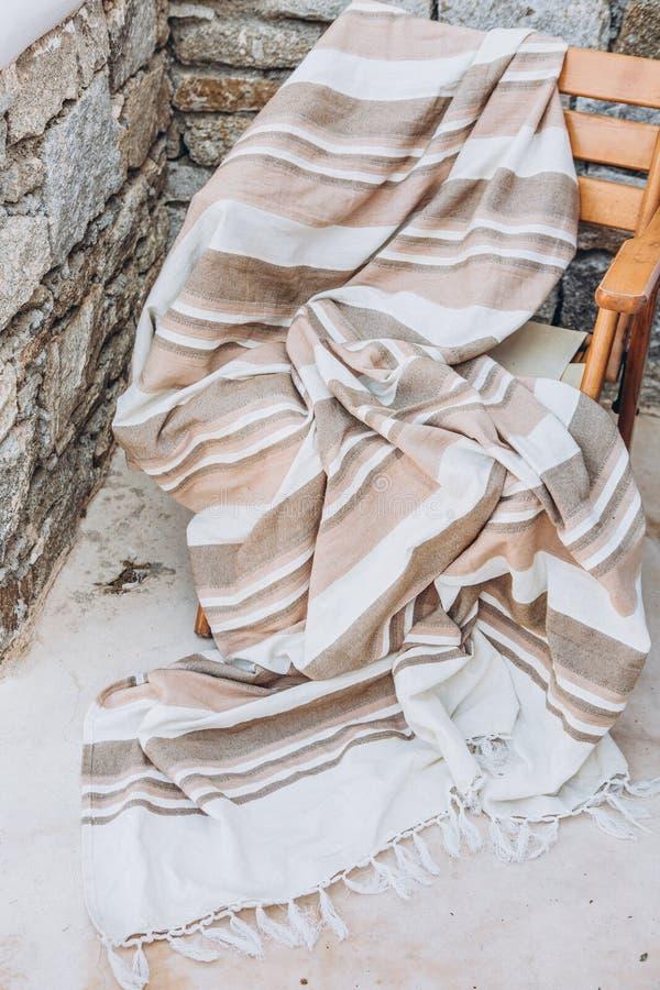 在石墙纹理之外的格子花呢披肩米黄椅子 库存图片
