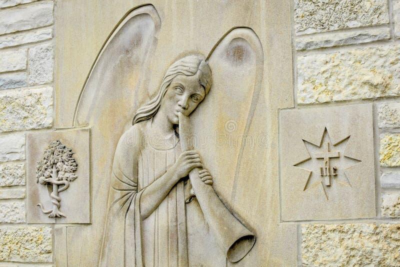 在石墙背景的天使宗教标志 免版税库存照片