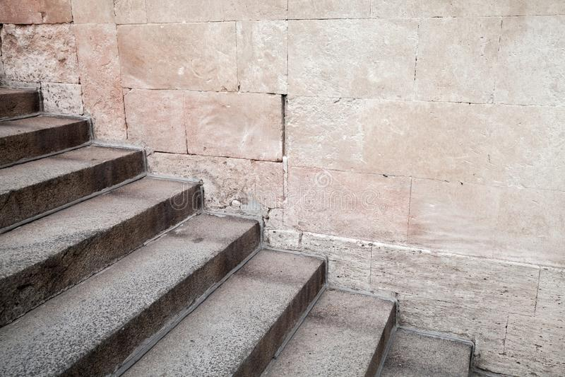 在石墙附近的空的老具体楼梯 库存照片