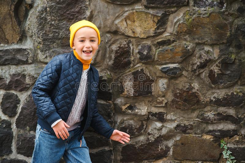 在石墙附近的逗人喜爱的时兴的男孩 孩子时尚概念 看对照相机和微笑的滑稽的孩子 夹克和帽子的时髦男孩 库存图片