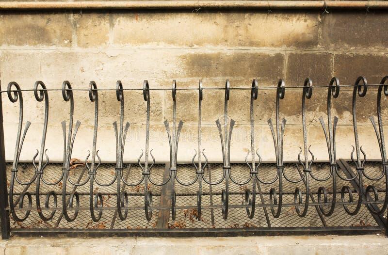 在石墙附近的黑金属篱芭 免版税库存图片