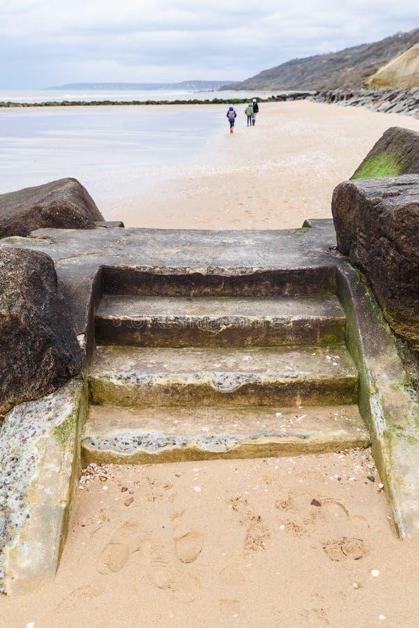 在石墙障碍的楼梯在海滩 免版税库存图片