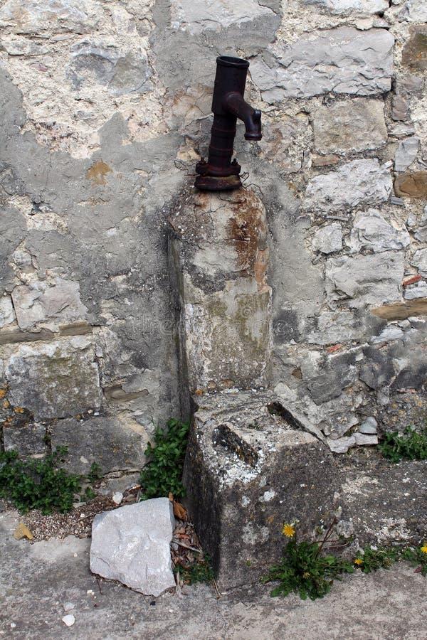 在石壁架的老生锈的手水泵 库存照片