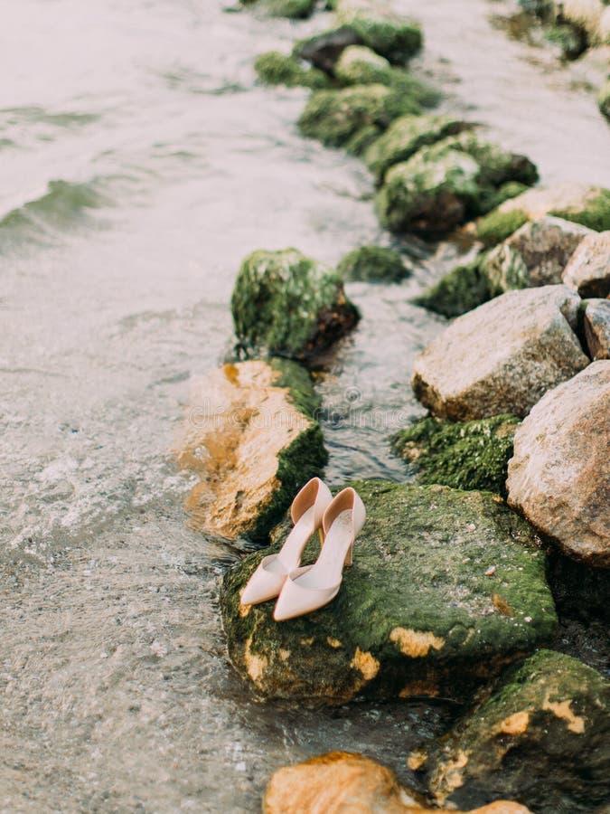 在石头安置的婚礼高跟鞋的垂直的看法长满与青苔在海附近 免版税库存图片