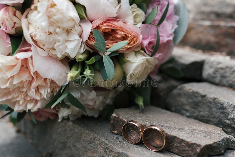 在石头的两金黄结婚戒指在白色和桃红色牡丹和玫瑰附近美丽的婚姻的花束在迷离户外 库存图片