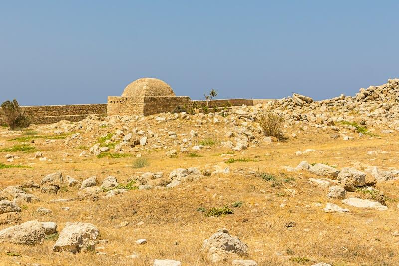 在石小山的希腊克利特堡垒Retinew老废墟与被烧焦的热草 免版税库存照片