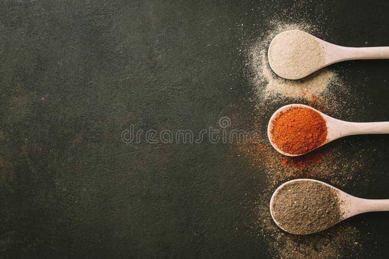 在石桌上的各种各样的香料匙子 与拷贝空间的顶视图 图库摄影
