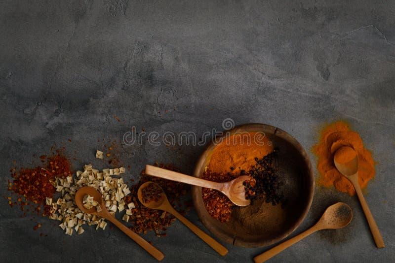 在石桌上的各种各样的香料匙子 与拷贝空间的顶视图 免版税库存图片