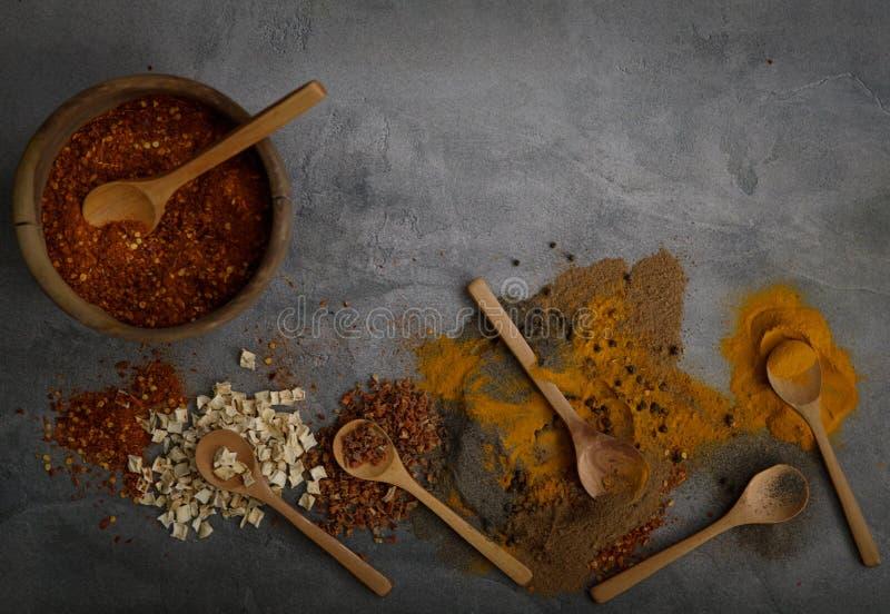 在石桌上的各种各样的香料匙子 与拷贝空间的顶视图 库存图片