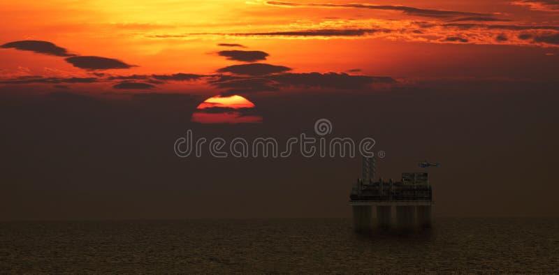 在石油平台的直升机着陆有美好的日落场面的 库存照片
