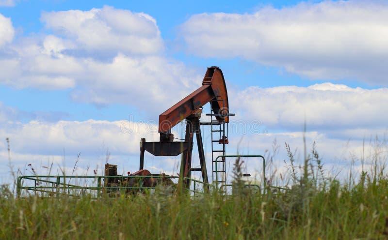 在石油的橙色运作的泵浦起重器或油井在绿色领域天际与坐在它旁边的水罐的化学制品和草和狂放的f 库存图片
