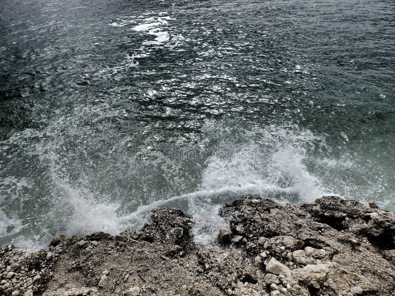 在石海滩的黑暗的巨浪 图库摄影