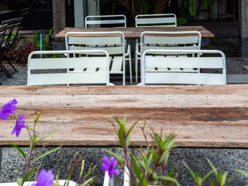 在石渣地板上的老室外木饭桌 免版税库存照片